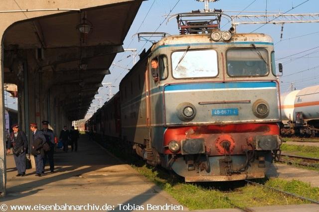 """Von Belgrad gibt es ins rumänische Timisoara (Temesvar) nur noch ein reservierungspflichtiges Schnellzugpaar pro Tag.Der Regionalverkehr wurde eingestellt. Dieser Schnellzug verlässt den Kopfbahnhof von Beograd gegen 16 Uhr. Bespannt ist er mit einer """"Kennedy"""" (Reihe 661). Diese steht jedoch bei der Abfahrt in Beograd nicht an der Westseite des Zuges sondern an der Ostseite am Prellbock: Bei der Abfahrt schiebt die 661 die Zuggarnitur ins Bahnhofsvorfeld und biegt von dort aus """"nach links"""" in die im Belgrader Stadtgebiet elektrifizierteStrecke ein. Diese verläuft wenige Kilometer parallel zur Donau, ehe sie diese bei Krnjaca überquert. Über Pancevo und Vrsac wird der rumänische EU-Außengrenzbahnhof Moravita erreicht. Dieser ist mittlerweile - wie schon beschrieben - mit Zäunen und Kameras gesichert und abends ausgeleuchtet wie ein Fußballfeld. Die Grenzbeamten haben sich unter dem Zug umgesehen und inspizierten auch in den Seitengängen der Schnellzugwagen die Hohlräume im Dach. Auf der weiteren Fahrt nach Timisoara kamen wir in Jebel vorbei, wo die Strecke nach Liebling mit seinem """"Alibi"""" - Malaxa-Zugpaar abzweigt. 18.04.2011:""""Krabbenkutter"""" 40 - 0671-4 im alten CFR - Design in Timisoara."""