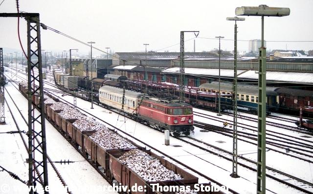 """Ein Intermezzo über etliche Jahre (1985 - 1999) blieb die """"Rollende Landstraße"""" nach Graz, hier mit ÖBB 1042 bei der Ausfahrt (Loks wurden stets von der ÖBB gestellt). Dies war einer der wenigen Verkehre, die später tatsächlich verlagert wurden (zunächst nach Regensburg Ost, heute Hafenbahnhof) und nicht wie fast alle anderen einst hier abwickelten Güterleistungen irgendwann (und das größtenteils noch vor Gründung der DB AG) sang- und klanglos eingestellt wurden. Die Zuckerrüben im Vordergrund (Ende nach Kampagne 1987) sind nur ein bekanntes Beispiel…"""