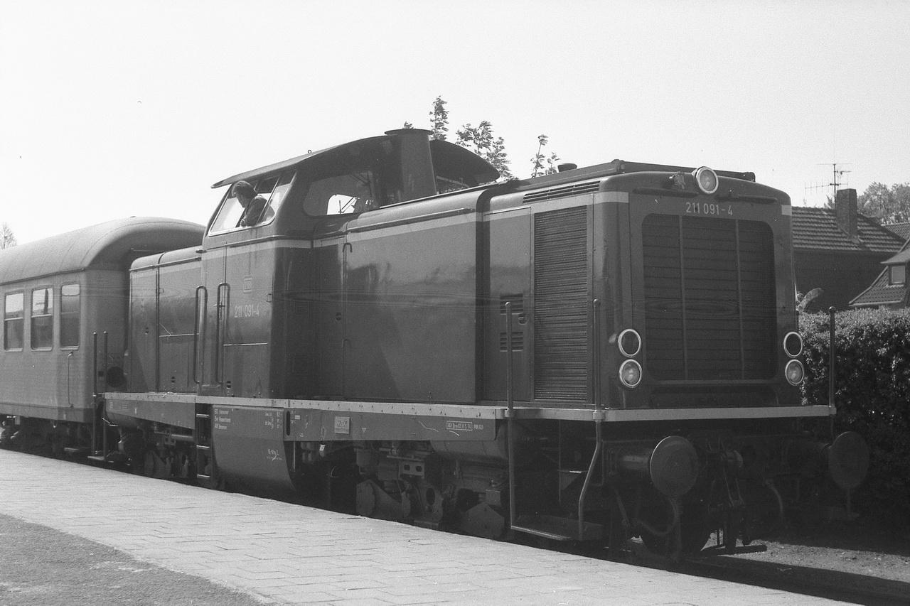 In Richtung Cuxhaven ging es wie zuvor schon im Oldenburger Land wieder per Diesel. Leider nicht mehr per Dampf, aber wenn man aus dem flächendeckend elektrifizierten Ruhrgebiet kam, waren Diesellokomotiven und nicht von der Oberleitung überspannte Strecken auch schon etwas Besonderes. Und so war mir der Zug mit der 211 091-4 durchaus ein Bild wert.