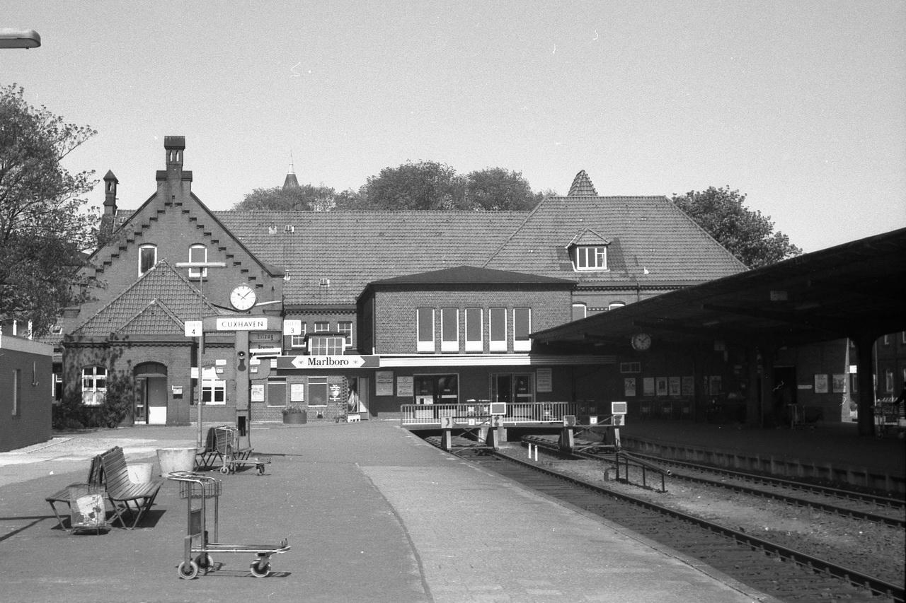 Ein Blick auf das Cuxhavener Empfangsgebäude. Der Hampelmann zeigt noch den gerade ausgefahrenen Eilzug nach Bremen an. Und auf dem Bahnsteig stehen die Koffer-Kulis.