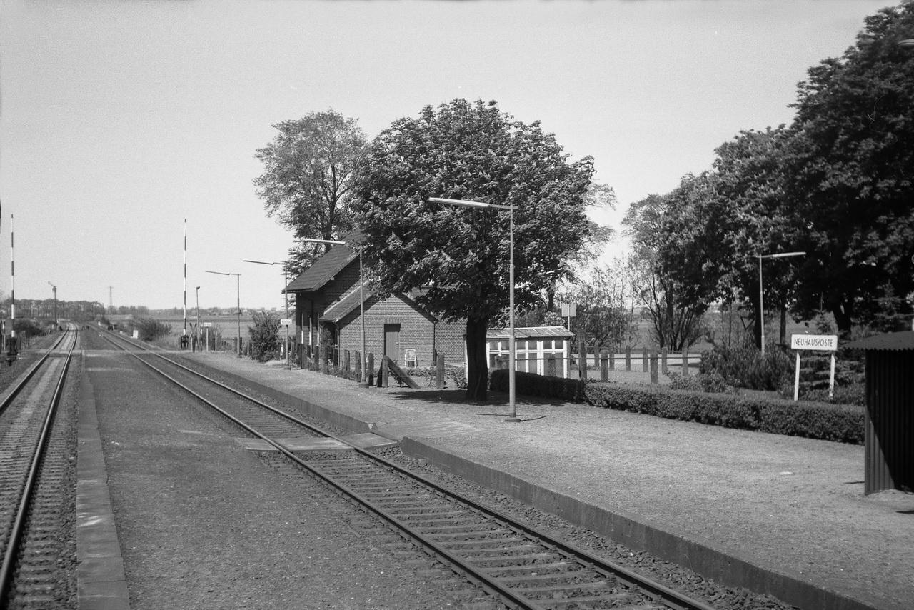 Langsam rollt der Zug aus dem Bahnhof Neuhaus-Oste, entlang dessen Bahnsteige wir hier blicken. Die Schranken sind längst wieder geöffnet, doch interessanterweise zeigt das Einfahrsignal noch immer freie Fahrt.