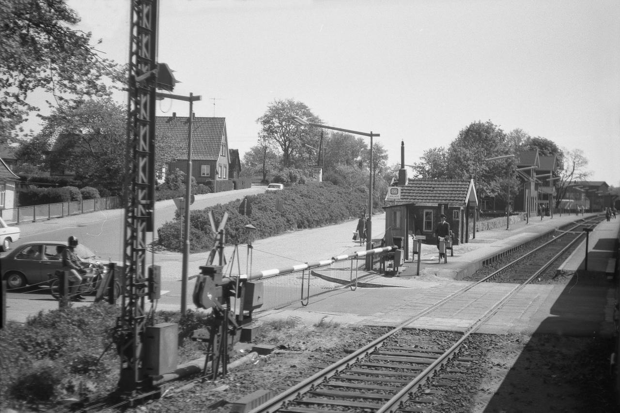 Nächste Station auf dem Weg nach Süden ist Cadenberge. Selbstverständlich wird die Schranke noch per Handkurbel geöffnet und geschlossen. Geduldig wartet der Schrankenwärter die Einfahrt des Zuges ab, auf den hinten am Bahnsteig einige Fahrgäste warten.