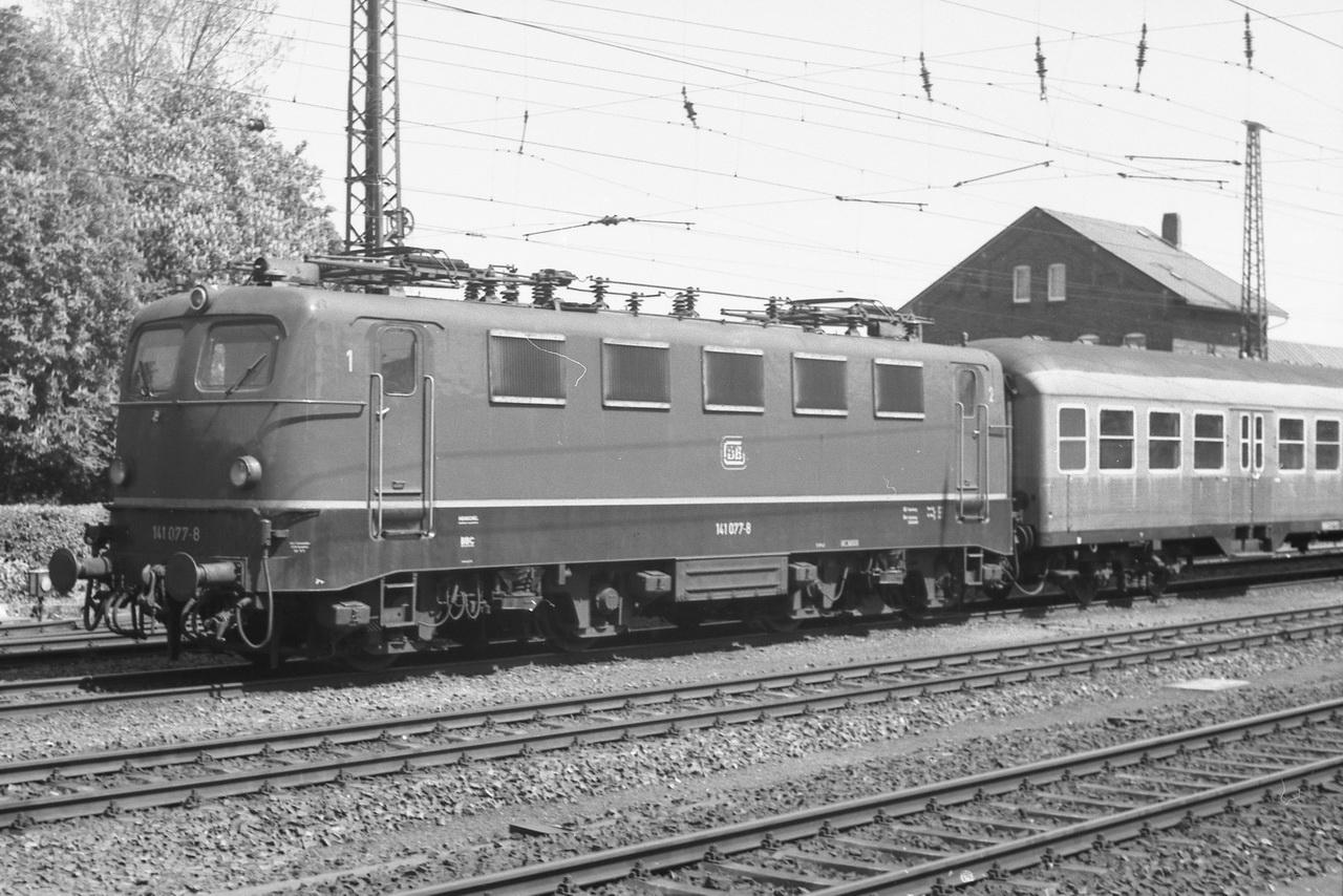"""Der typische Nahverkehrszug jener Jahre - ein """"Knallfrosch"""" und """"Silberlinge"""". Hier die 141 077-8. Während ihre Schwester 141 072-9, die gerade den Bahnhof verlassen hat, noch die alten Lüftungsgitter und das silberne Dach mit Regenrinne hatte, ist sie schon modernisiert. Dafür hat sie noch die alten Lampen."""
