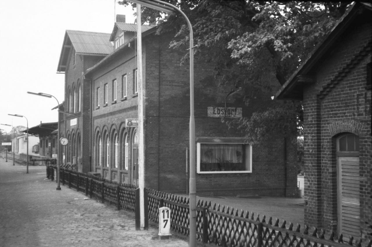 Der Tag geht zu Ende. Aus dem Fenster des knatternden Schienenbusses nach Langwedel, von wo eszurück nach Nienburg geht, gelingt ein Bild des Bahnhof Ebstorf. Der Ort ist bekannt durch sein Kloster und die darin befindliche Weltkarte. Die Bahnstrecke von Uelzen nach Langwedel erlangte als kürzeste Verbindung von Berlin zum Marinestützpunkt in Wilhelmshaven in der Zeit vor dem ersten Weltkrieg eine herausragende Bedeutung und wurde 1907 zweigleisig ausgebaut. Davon ist 1977 nichts mehr zu spüren, der Rückbau zu einer eingleisigen Nebenbahn hatte begonnen.