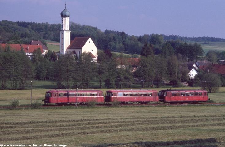 """Erwähnenswert ist noch das sogenannte """"Angebot"""" am Wochenende mit dem Bus: Samstag ab 6:17 Uhr Mittelneufnach – Gessertshausen und zurück von Augsburg nach Mittelneufnach an 14:20 Uhr. Noch """"besser"""" war der Sonntag, an dem man um 9:58 Uhr von Langenneufnach nach Augsburg und um 17:07 Uhr von Fischach nach Augsburg fahren konnte, zurück jedoch überhaupt nicht. 29.05.1991: 798 795 mit N 6060 vor der Kirche von Langenneufnach. Damals eines der besten Motive der Strecke, heute steht hier ein Wohngebiet."""